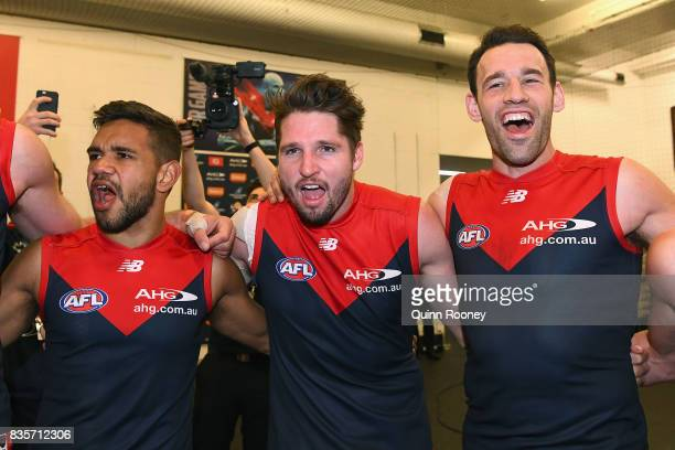 Neville Jetta Jesse Hogan and Cameron Pedersen of the Demons sing the song in the rooms after winning the round 22 AFL match between the Melbourne...