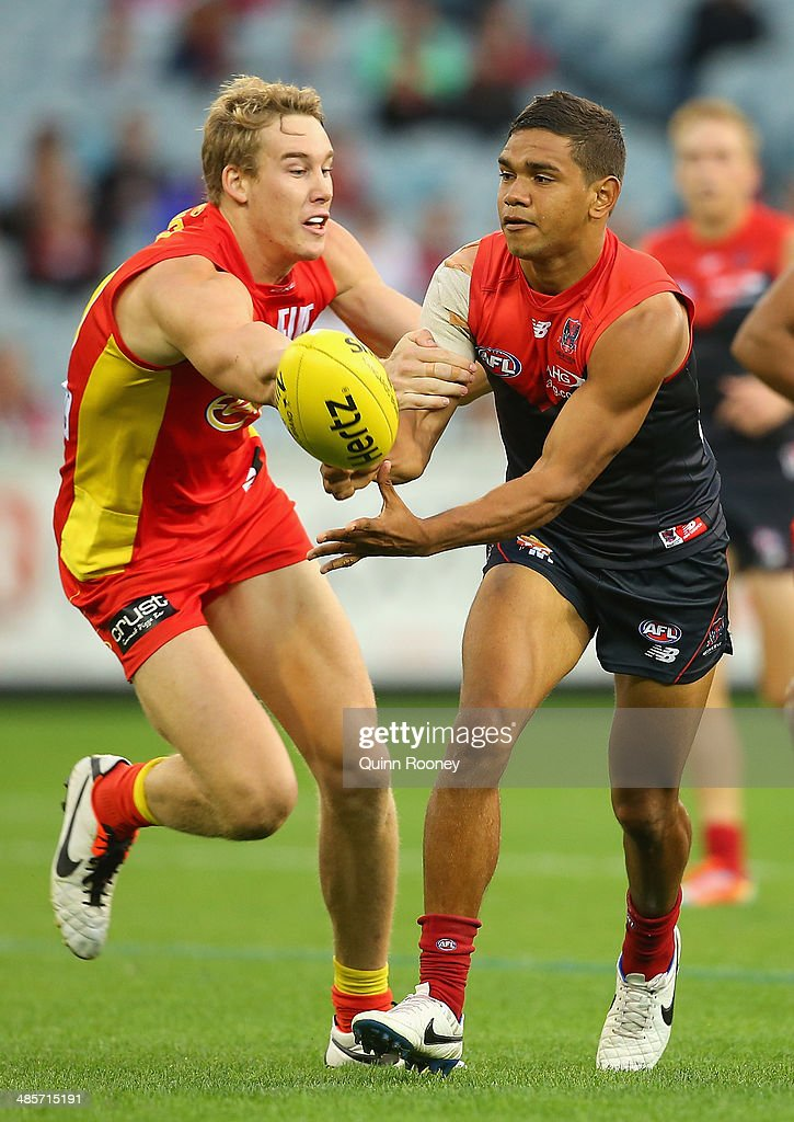 Neville Jetta of the Demons handballs whilst being tackled by Tom Lynch of the Suns during the round five AFL match between the Melbourne Demons and the Gold Coast Suns at Melbourne Cricket Ground on April 20, 2014 in Melbourne, Australia.