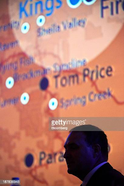 Neville 'Nev' Power chief executive officer of Fortescue Metals Group Ltd sits silhouetted against a map of Western Australia's Pilbara region during...