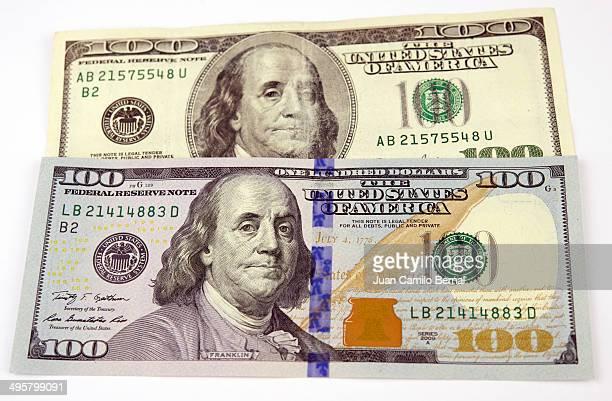 New $100 dollars bill on top of old bill