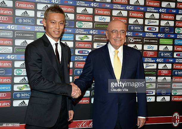 New AC Milan player Japanese midfielder Keisuke Honda poses with AC Milan CEO Adriano Galliani during a press conference at San Siro Stadium on...