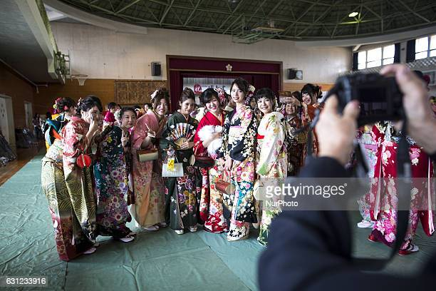 New adults in kimonos takes photos after attending a Coming of Age Day celebration ceremony in Shuri Junior High School in Okinawa Japan on January 8...