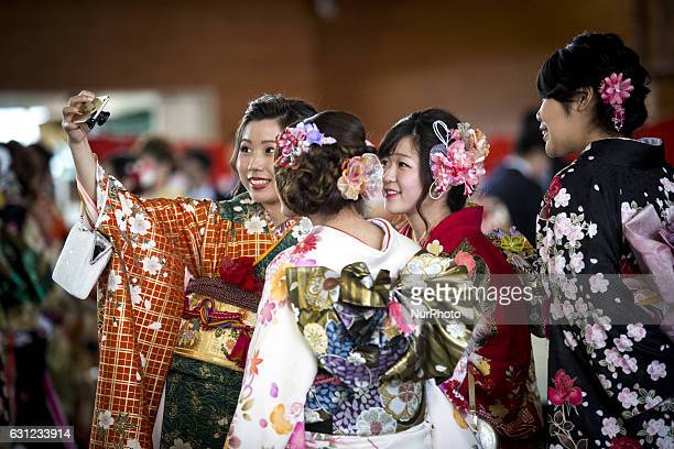 New adults in kimonos takes selfies after attending a Coming of Age Day celebration ceremony in Shuri Junior High School in Okinawa Japan on January...