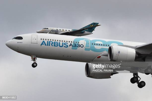 A new Airbus A330neo is about to land after its first flight as a helicopter films its landing on October 19 at the ToulouseBlagnac airport near...