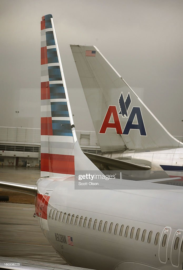 A new American Airlines 737-800 aircraft (L) featuring a new paint job sits at a gate at O'Hare Airport as an aircraft with the old tail design passes by on January 29, 2013 in Chicago, Illinois. This year, American plans to take delivery of nearly 60 new aircraft featuring the logo and paint. American currently has a fleet of nearly 900 aircraft that fly more than 3,500 daily flights worldwide.