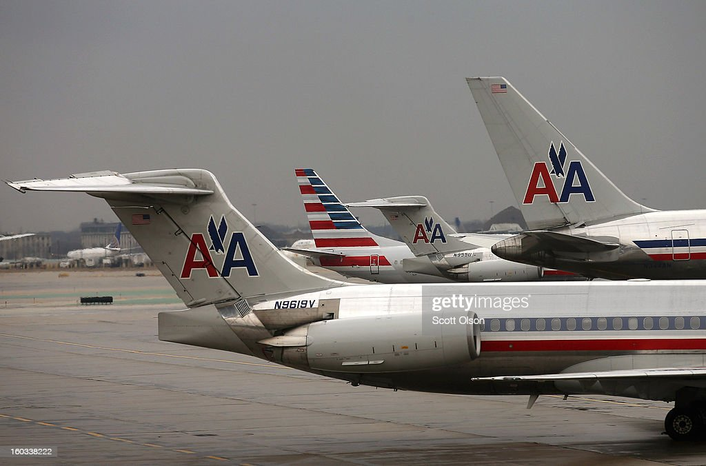 A new American Airlines 737-800 aircraft (2nd from left) featuring a new tail design sits at a gate at O'Hare Airport on January 29, 2013 in Chicago, Illinois. This year, American plans to take delivery of nearly 60 new aircraft featuring the logo and paint. American currently has a fleet of nearly 900 aircraft that fly more than 3,500 daily flights worldwide.