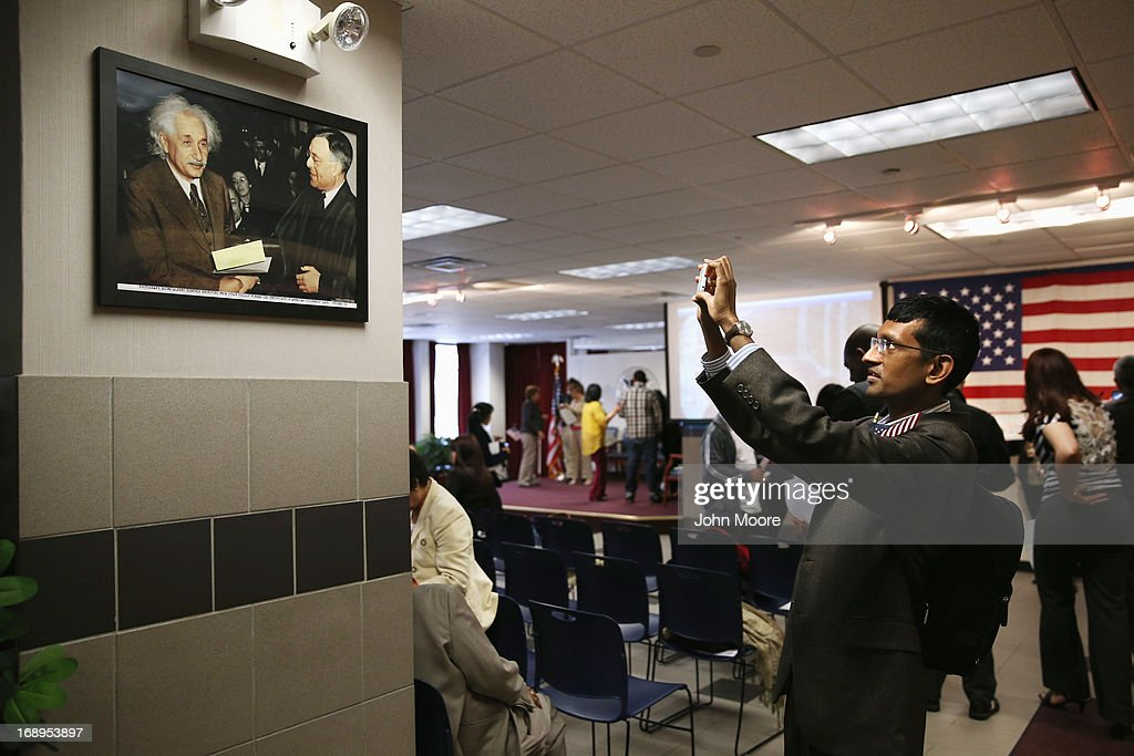 New American citizen Deepak Subburam from Singapore takes photos of Albert Einstein, who was also a naturalized American, at a naturalization ceremony held at the U.S. Citizenship and Immigration Services (USCIS), office on May 17, 2013 in New York City. One hundred and fifty immigrants from 38 different countries became U.S. citizens at the event. Some 11 million undocumented immigrants living in the U.S. stand to eventually gain American citizenship if Congress passes immigration reforms currently being negotiated.