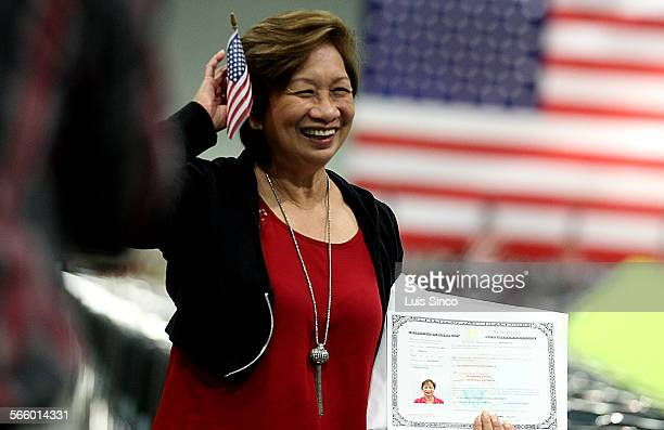New American citizen Marie Quines a native of the Philippines poses for souvenir pictures following a naturalization ceremony Wednesday Aug 21 at the...