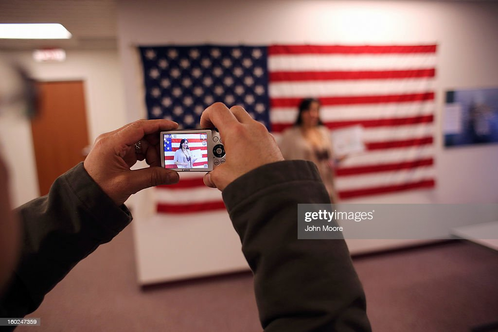 New American citizens take photos following a naturalization ceremony at the district office of U.S. Citizenship and Immigration Services (USCIS) on January 28, 2013 in Newark, New Jersey. Some 38,000 immigrants became U.S. citizens at the Newark office alone in 2012.