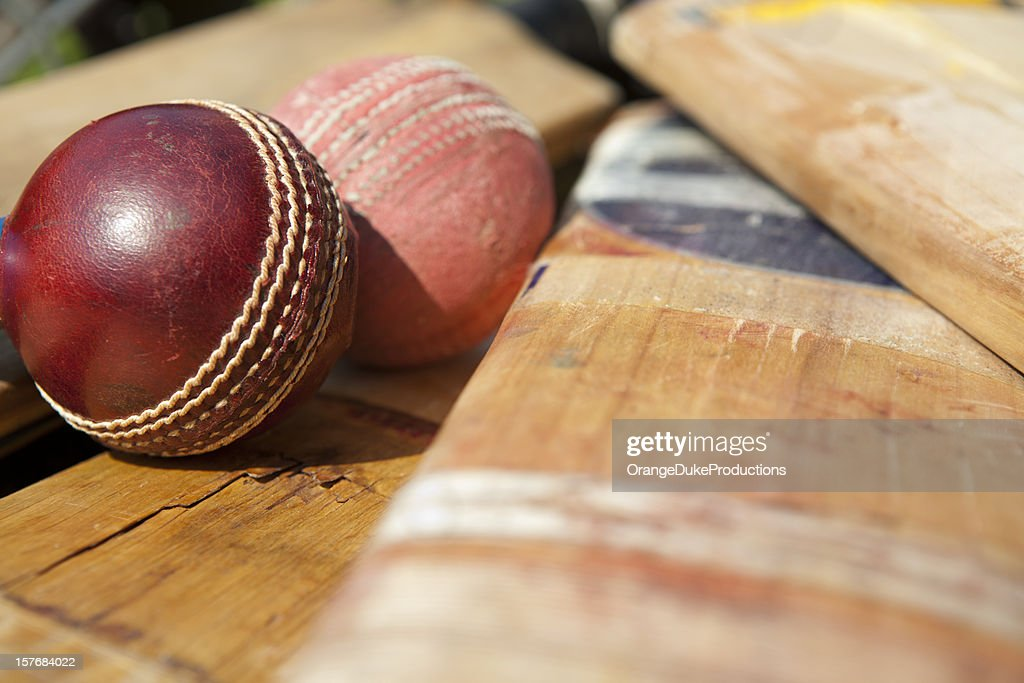 New and old cricket ball lying on bats