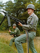 New Army Weapons in Action Sergeant Harry M Mayer foreground with the M60 Machine Gun and SFC George Evans with the M14 Rifle demonstrate the two...