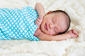 New Baby Boy sleeping wrapped in blue and white checked wrap on cream fur rug with arms out - caucasian and pacific islander ethnicity
