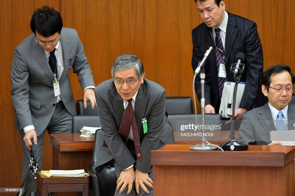 New Bank of Japan governor Haruhiko Kuroda (C, bottom) bows to members of the lower house finance committee prior to a committee session at the parliament in Tokyo on March 26, 2013. Kuroda has been appointed to head the bank for only three weeks through April 8, when the term of his predecessor will formally end.