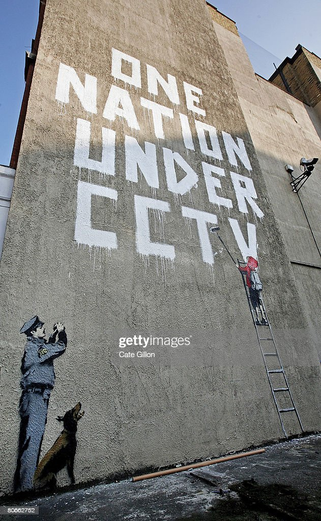 A new Banksy graffiti work on a private property catches the eye of passers by on April 14, 2008 in London, England. The work, which depicts a child painting the words 'One Nation Under CCTV' with a security guard watching him is situated under a security camera and has appeared sometime between the hours of Saturday and Monday morning.