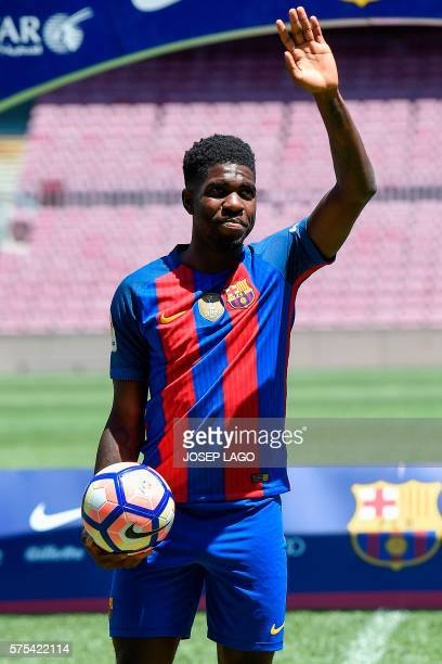 New Barcelona's French defender Samuel Umtiti waves supporters from the pitch during his official presentation at the Camp Nou stadium in Barcelona...
