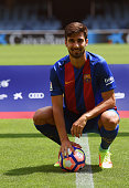 New Barcelona's Portuguesse forward Andre Gomes poses with his new jersey and a ball during his official presentation at the Camp Nou stadium in...
