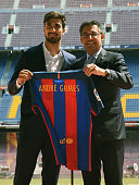 New Barcelona's Portuguesse forward Andre Gomes poses with his new jersey beside Barcelona's president Josep Maria Bartomeu on the pitch during his...