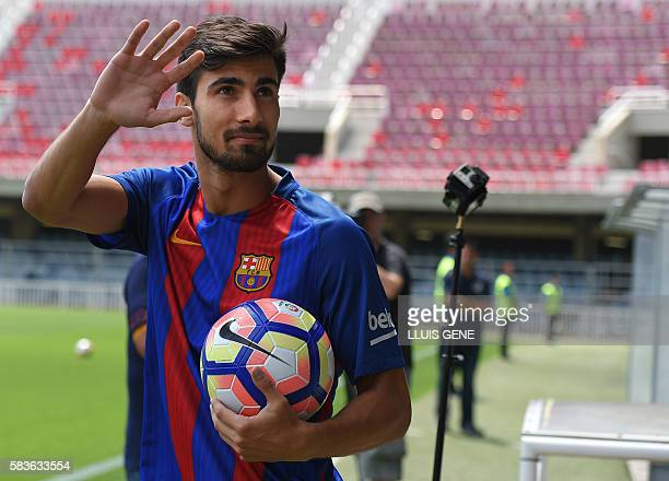New Barcelona's Portuguesse forward Andre Gomes waves as he arrives on fiels for his official presentation at the Camp Nou stadium in Barcelona on...