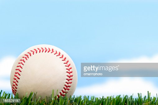 New Baseball in Grass against blue sky