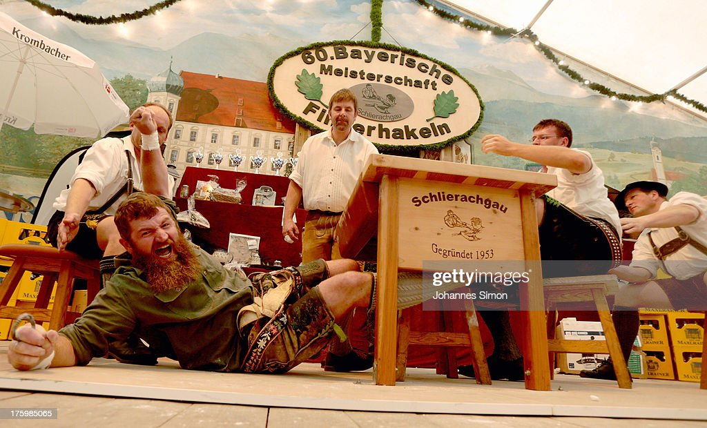 New Bavarian middle weight champion Toni Bader (L) of Oberammergau celebrates after winning the final fight against vice champion Korbinian Fischer of Bad Kohlgrub during the 60th annual Bavarian finger wrestling championships (also known as Fingerhakeln) on August 11, 2013 in Feldkirchen-Westerham, Germany. The sport involves two competitors matched in class according to age and weight who sit at a specifically-designed table across from one another and pull at a small leather band with one finger until one player has pulled the other across. The sport is traditional in Bavaria and as well Austria and dates back to the 17th century.