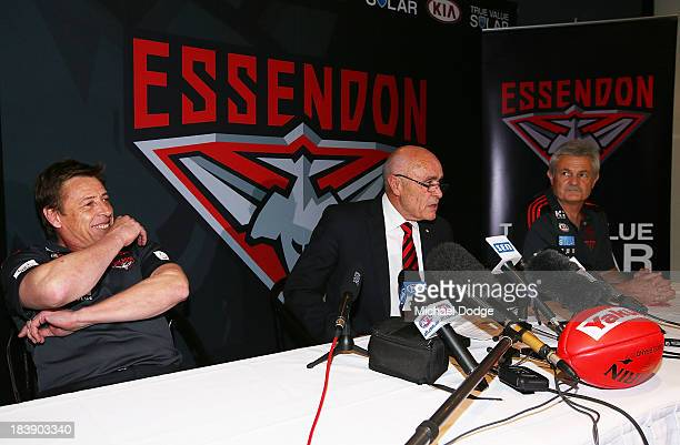 New Bombers coach Mark Thompson reacts next to Chairman Paul Little and new Senior assistant coach Neil Craig after dropping his mobile phone during...
