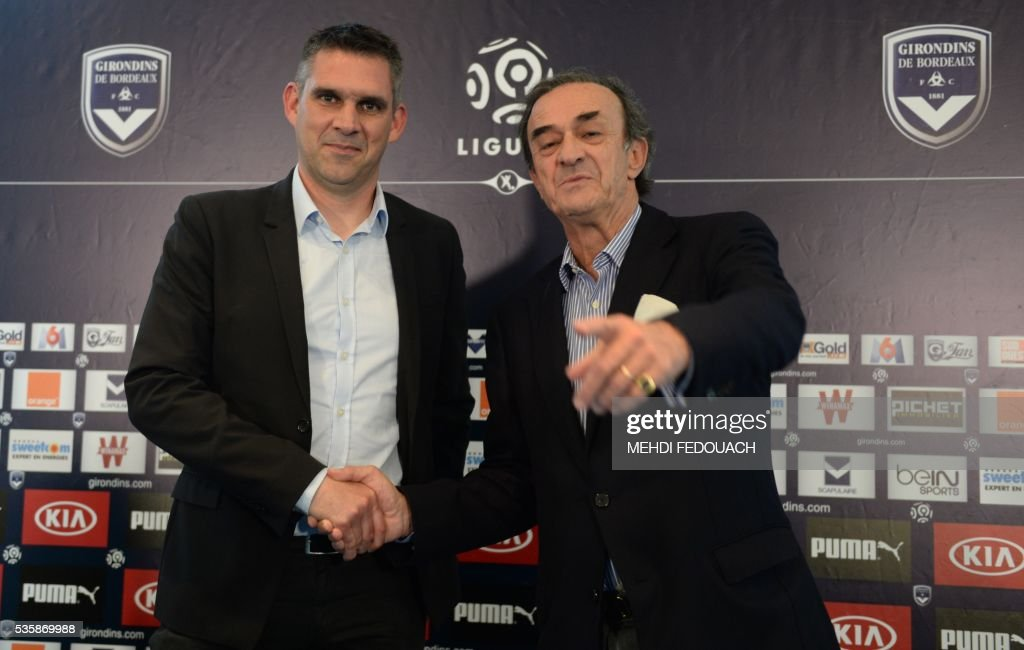 New Bordeaux' head coach Jocelyn Gourvennec (L) shakes hands with Bordeaux' president Jean-Louis Triaud after a press conference on May 30, 2106 in Le Haillan, near Bordeaux, southwestern France. / AFP / MEHDI