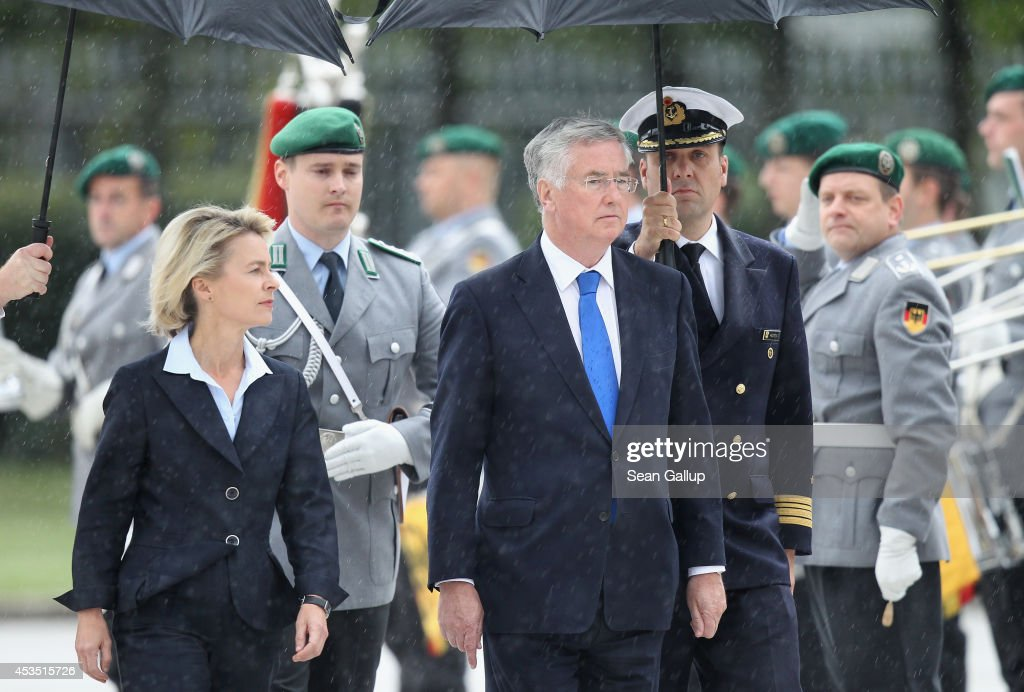 New British Defence Secretary Michael Fallon (R) and German Defence Minister <a gi-track='captionPersonalityLinkClicked' href=/galleries/search?phrase=Ursula+von+der+Leyen&family=editorial&specificpeople=4249207 ng-click='$event.stopPropagation()'>Ursula von der Leyen</a> review a guard of honour under rain upon Fallon's arrival at the German Defence Ministry on August 12, 2014 in Berlin, Germany. This is Fallon's first visit to the German capital since he took office.