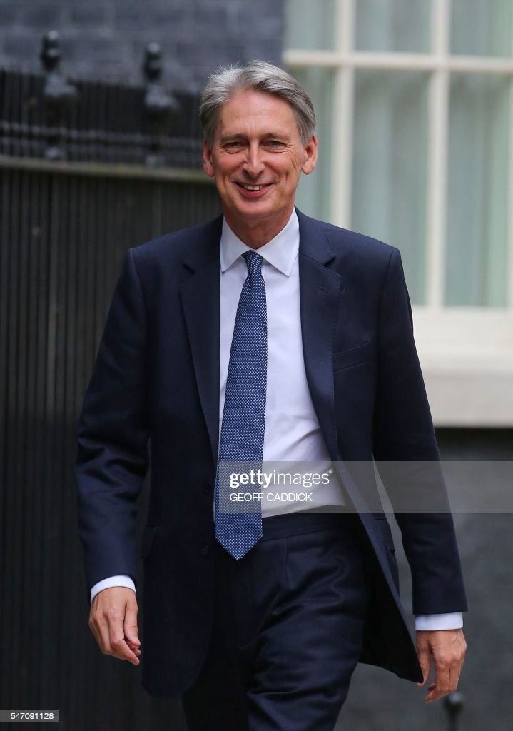 New British Finance Minister Philip Hammond walks to 10 Downing Street in central London on July 13 after New British Prime Minister Theresa May took...