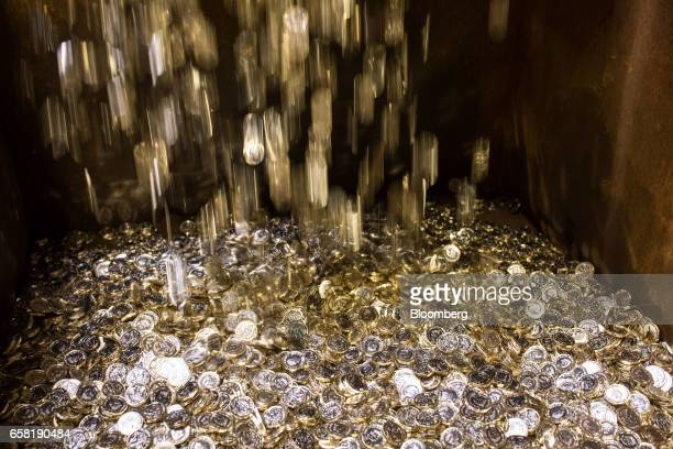 New British one pound coins drop into a container during their production at The Royal Mint in Llantrisant UK on Thursday March 23 2017 Britain's...