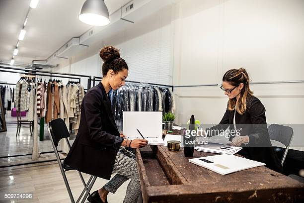New Business clothing store, women at work on contracts