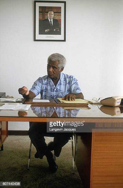 New Caledonia stateman Dick Ukeiwe works in his office under a photograph of French President Francois Mitterrand In the French overseas territory of...