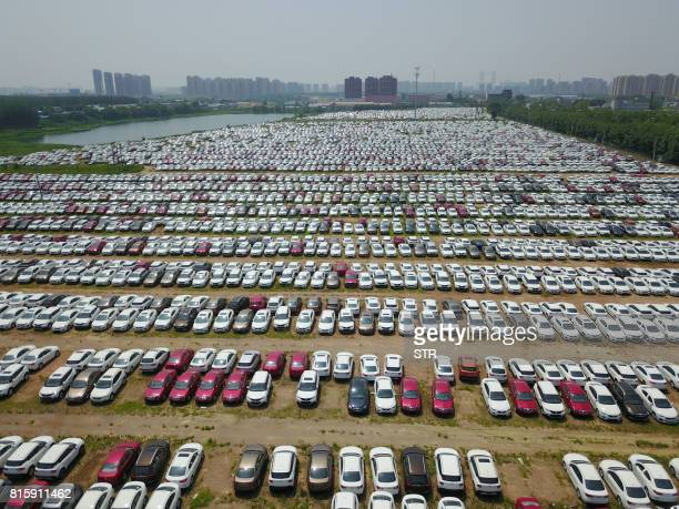 New cars are seen in a parking lot of the Brilliance factory in Shenyang in China's northeast Liaoning province on July 17 2017 China posted...
