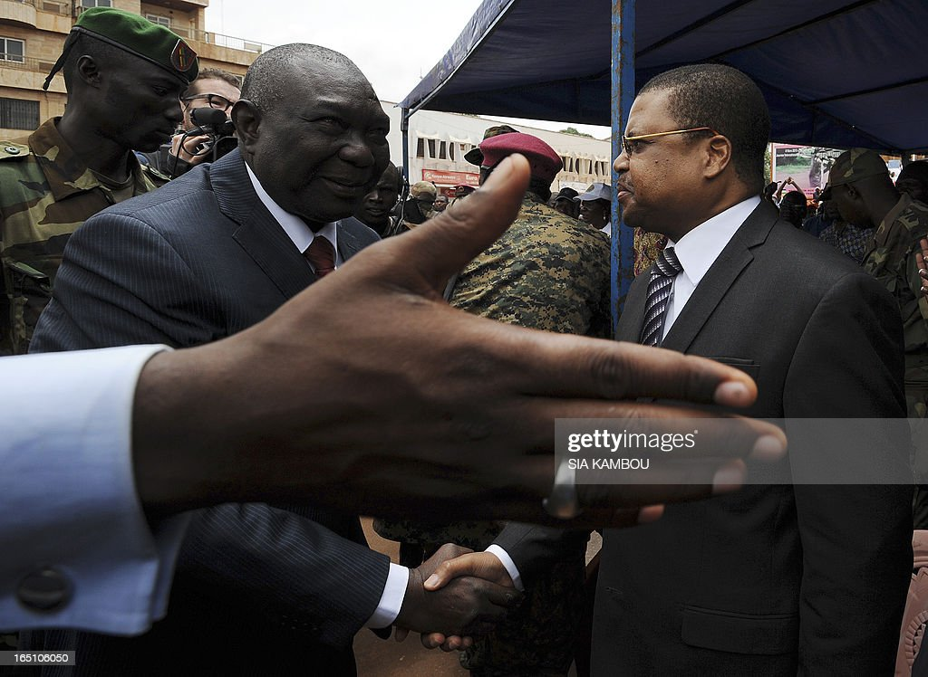 New Central African Republic leader Michel Djotodia (L) shakes hands with with Prime Minister Nicolas Tiangaye on Republic Plaza in Bangui on March 30, 2013 . The Central African Republic's new strongman Michel Djotodia vowed Saturday not to contest 2016 polls and hand over power at the end of the three-year transition he declared after his coup a week ago. AFP PHOTO / SIA KAMBOU