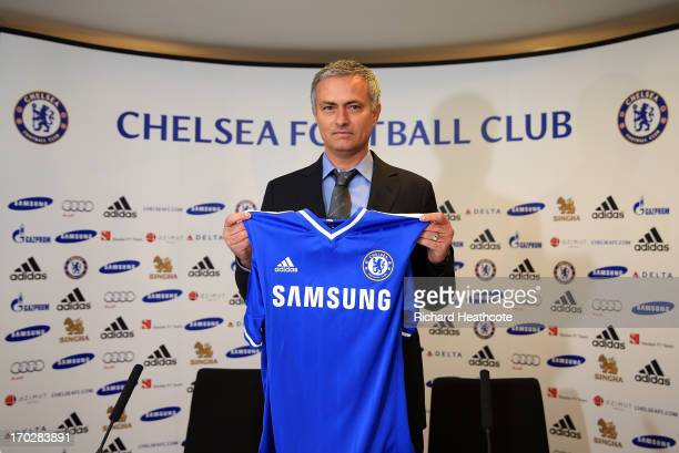 New Chelsea manager Jose Mourinho holds up the shirt before the Chealsea FC press conference at Stamford Bridge on June 10 2013 in London England...