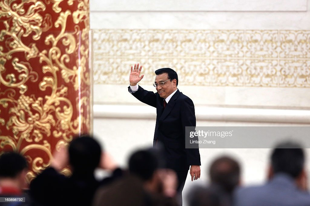 New Chinese Premier Li Keqiang waves goodbye after during his first press conference at the Great Hall of the People on March 17, 2013 in Beijing, China. Li Keqiang was elected as China's Premier last Friday at the 12th National People's Congress, the country's top legislature.