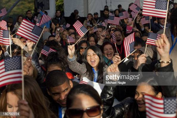 New citizens cheer and wave at a naturalization ceremony at Liberty Island on October 28 2011 in New York City 125 citizens were naturalized in honor...