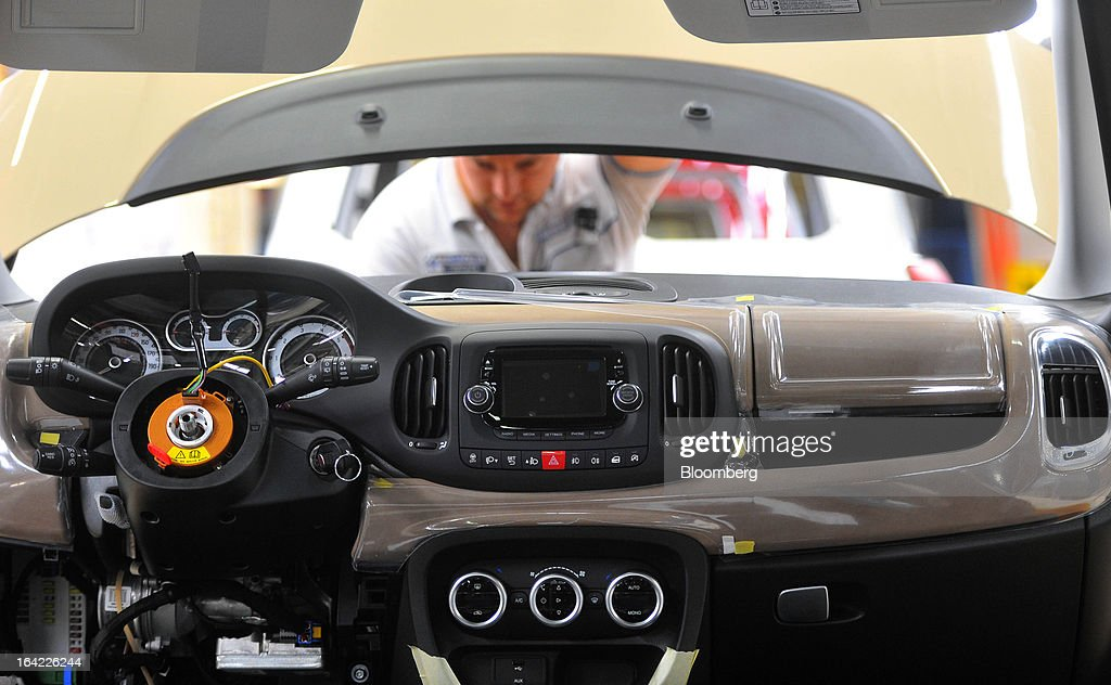 A new dashboard assembly is seen while an employee works on a Fiat 500L automobile on the production line at the Fiat Automobili Srbija plant in Kragujevac, Serbia, on Wednesday, March 20, 2013. Fiat Automobili Srbija, a joint venture between the government and Italian carmaker Fiat, is Serbia's sole automaker. Photographer: Oliver Bunic/Bloomberg via Getty Images