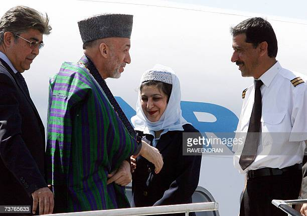 Afghan President Hamid Karzai talks with Ariana Afghan Airlines crew members upon his arrival at the Indian Air Force Station at Palam in New Delhi...