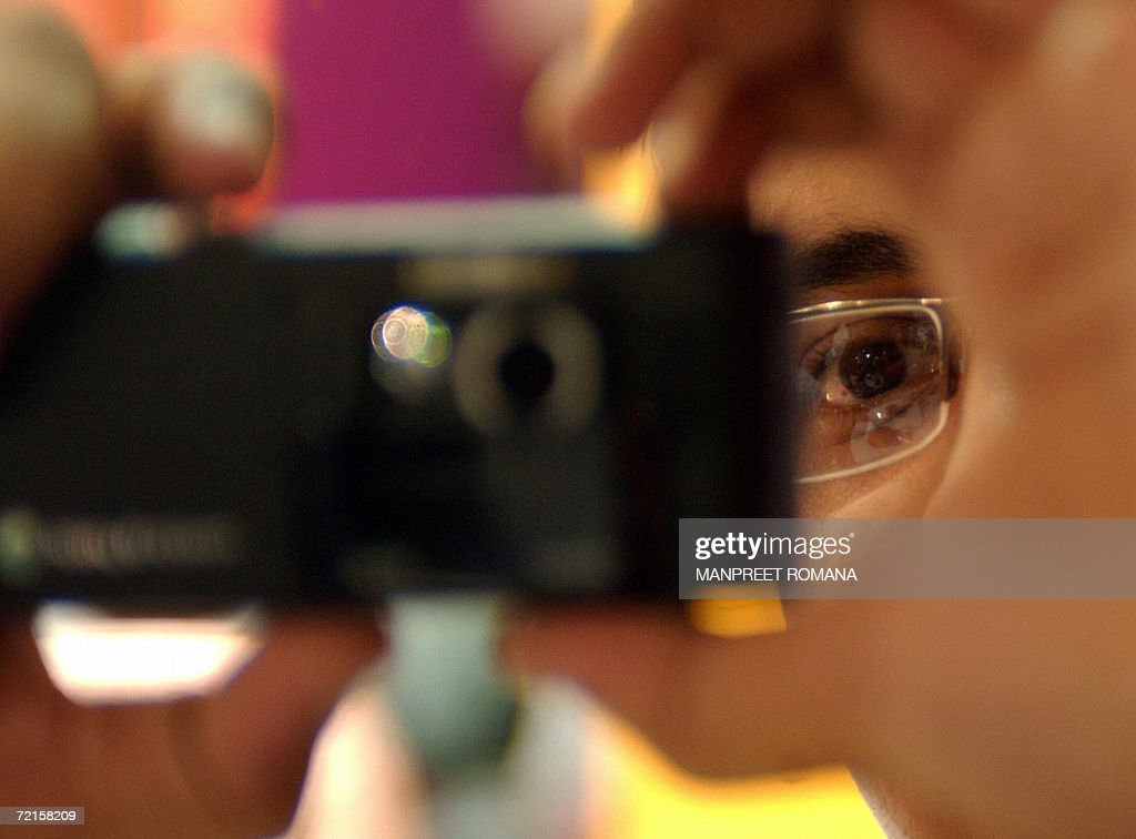 An Indian customer takes a photograph with a cellular telephone during the 'Mobile Asia 2006' exhibition in New Delhi 13 October 2006 'Mobile Asia...