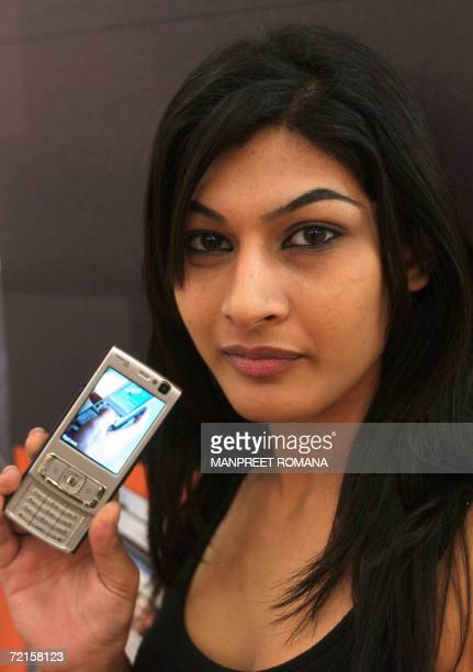 An Indian model poses with a Nokia N95 cellular telephone during the 'Mobile Asia 2006' exhibition in New Delhi 13 October 2006 'Mobile Asia 2006' is...