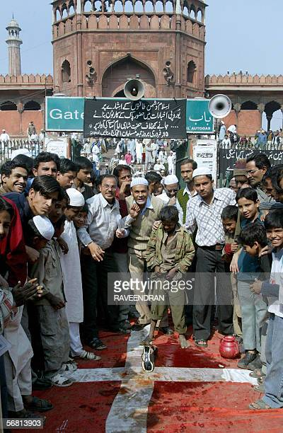 An Indian Muslim boy urinates on a Danish flag which lies on the road outside the Jama Masjid in New Delhi 10 February 2006 during an anticartoon...