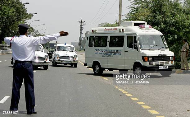 An Indian traffic policeman gestures as an Army ambulance carrying Indian External Affairs Minister Pranab Mukherjee drives in convoy into the...