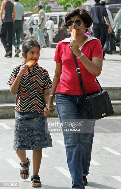 An Indian woman and her child eat ice cream to cool themselves from the heat in New Delhi 17 April 2007 Temperatures across the country have reached...