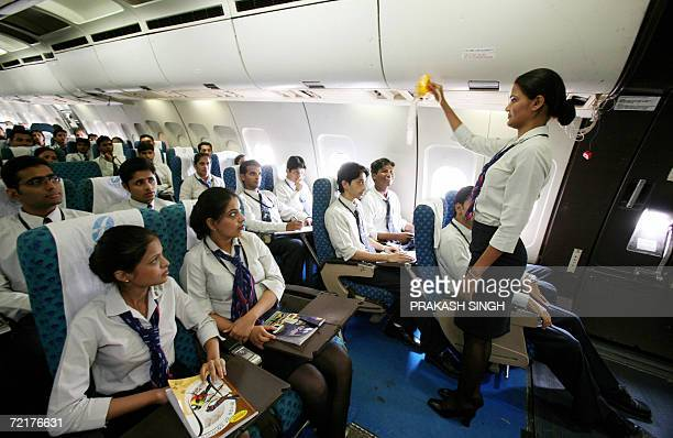In this photograph dated 23 August 2006 Indian cabin crew students learn use of emergency oxygen masks on a real Airbus A300 aircraft stationed at...