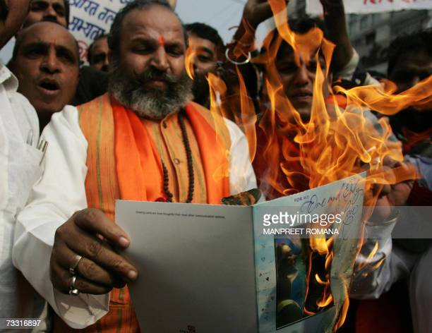 Indian activists of the Hindu fundamentalist Shiv Sena party shout slogans and burn Valentine's Day greetings cards in protest against Valentine's...