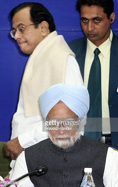 Indian Finance Minister P Chidambaram passes by Indian Prime Minister Manmohan Singh during a Chief Ministers conference on pension reforms in New...