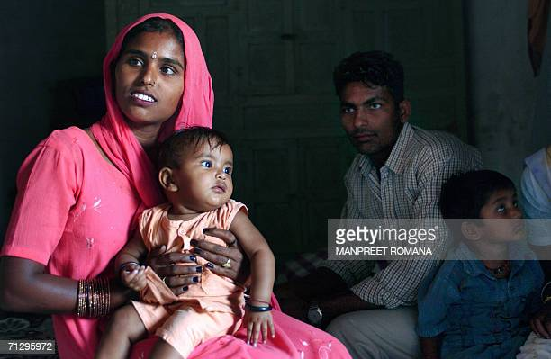 Indian mother Sangeeta Sidhu holds her eight month old daughter Nandani as her husband looks on in their home in the village of Jalahmajra in...