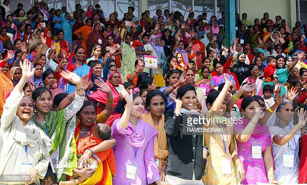 Indian women wave to unseen President of India's Congress Party and Chairperson of the country's United Progressive Alliance government Sonia Gandhi...
