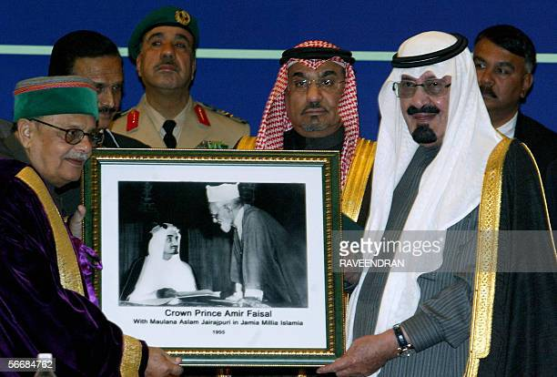 India's Minister for Human Resource Development Arjun Singh presents a photograph featuring an image of Crown Prince Amir Faisal with Maulana Aslam...
