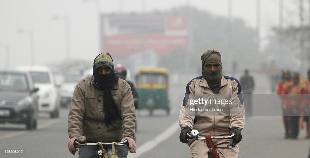 New Delhi, India - January 03 - Cyclists daring chilling cold as temperature remains low in New Delhi on Thursday, January 03 2013. A cold wave is sweeping across north India sending temperatures plunging. Delhi Wednesday witnessed the coldest day in the past 44 years.